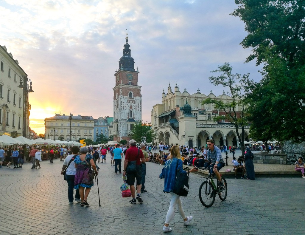 Sunset on Krakow Market Square with people walking and cycling