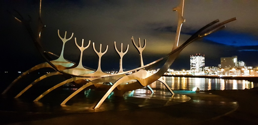 The Sun Voyager in Reykjavik illuminated with the city lights in the back.