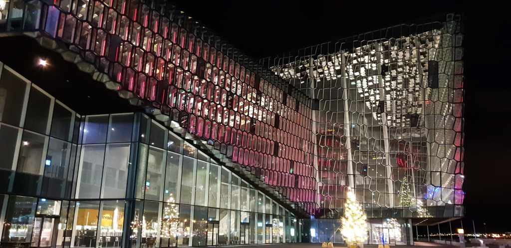 Reykjavik Concert Hall Harpa with pink and with light moving along the facade.