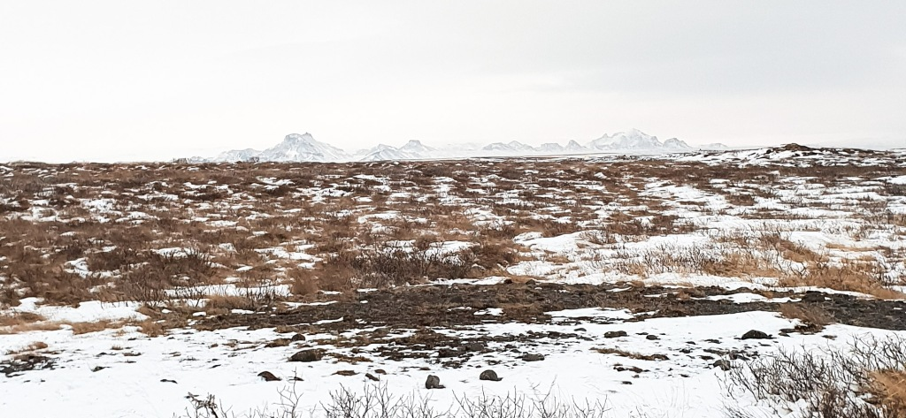 Vast, flat landscape on Iceland with some snow and mountain range in the background