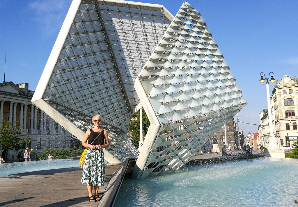 a woman in skirt standing in front of a modern fontain in Poznan