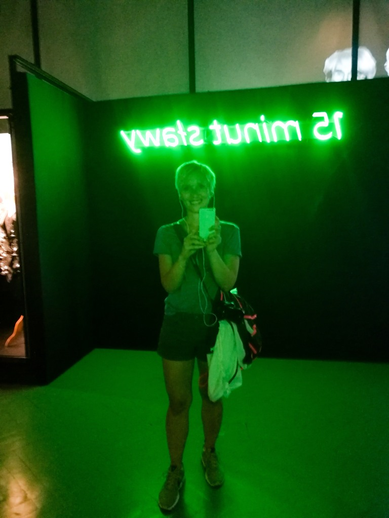 A woman taking a selfie in a room with green light.