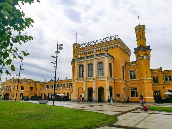 The yellow station building in Wroclaw with two spires and people walking outside.