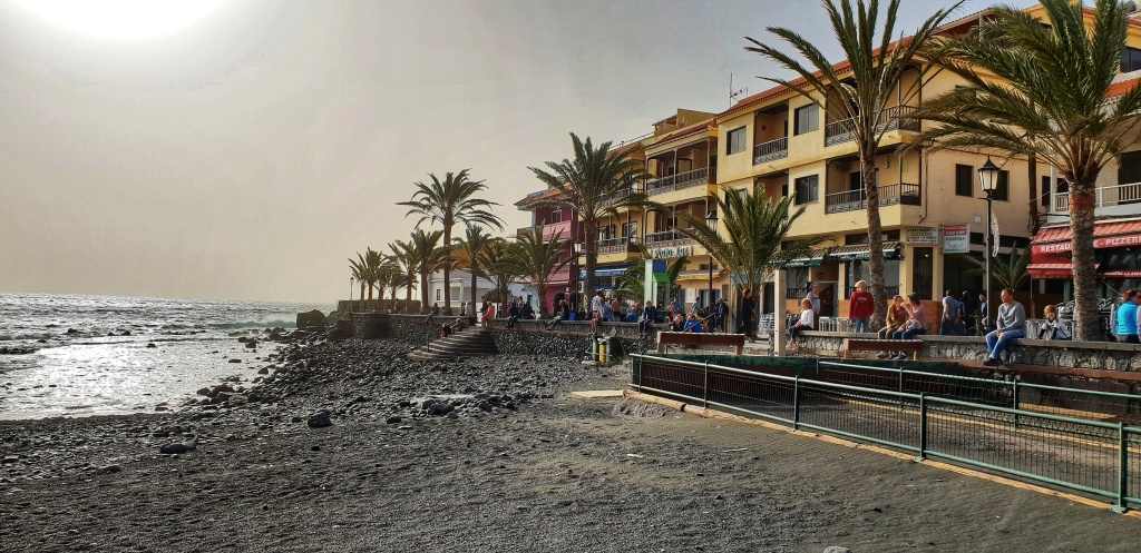 The black beach and yellow buildings on the promenade in Valle Gran Rey