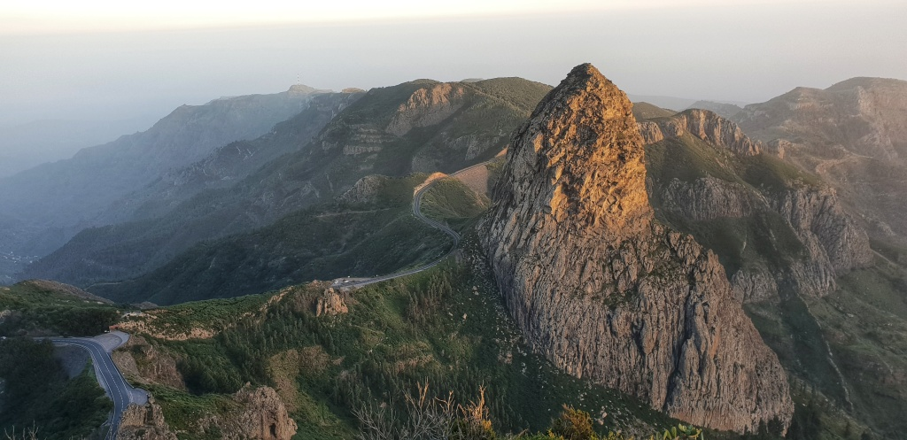 A winding road and a large rock formation in sunset on La Gomera.