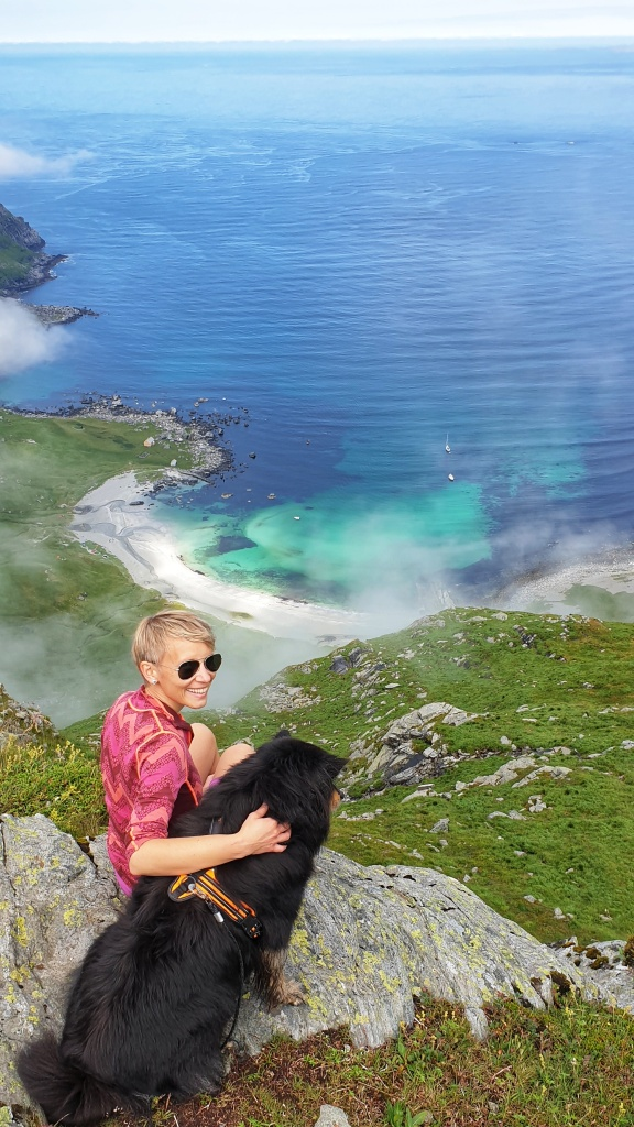 A smiling woman and a black dog in the hillside above Vetvika beach