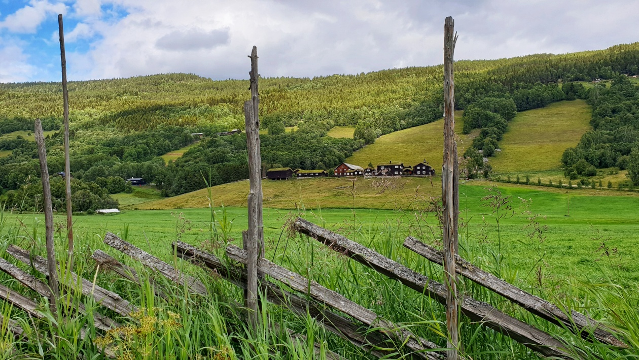 An old farm in Heidal seen behind a fence surrounded by green fields