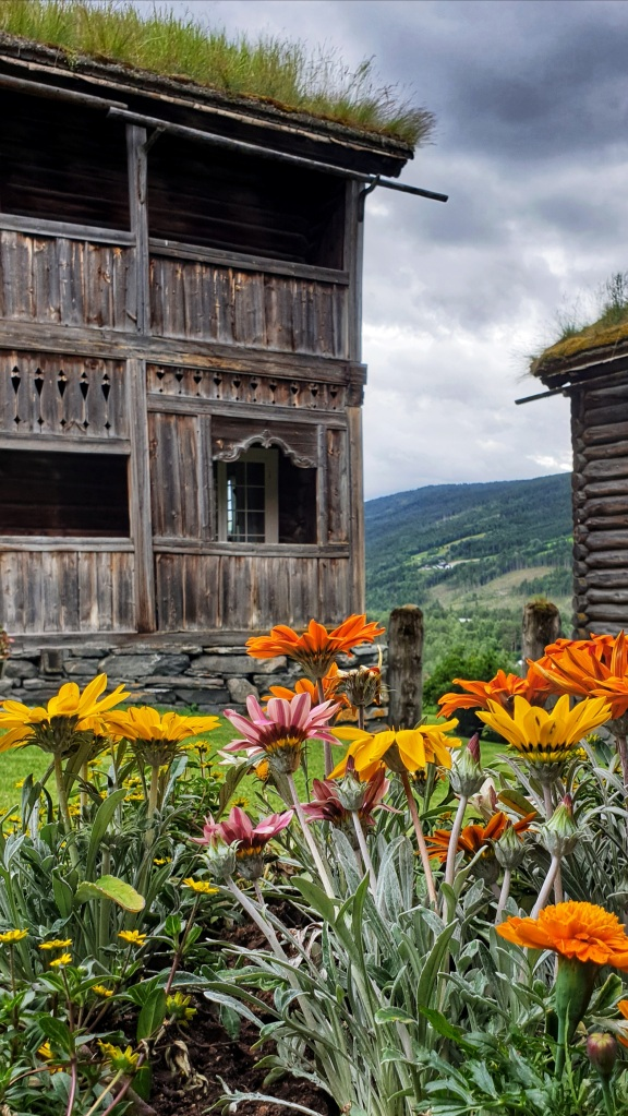 Old listed houses in Heidal with colourful flowers in front