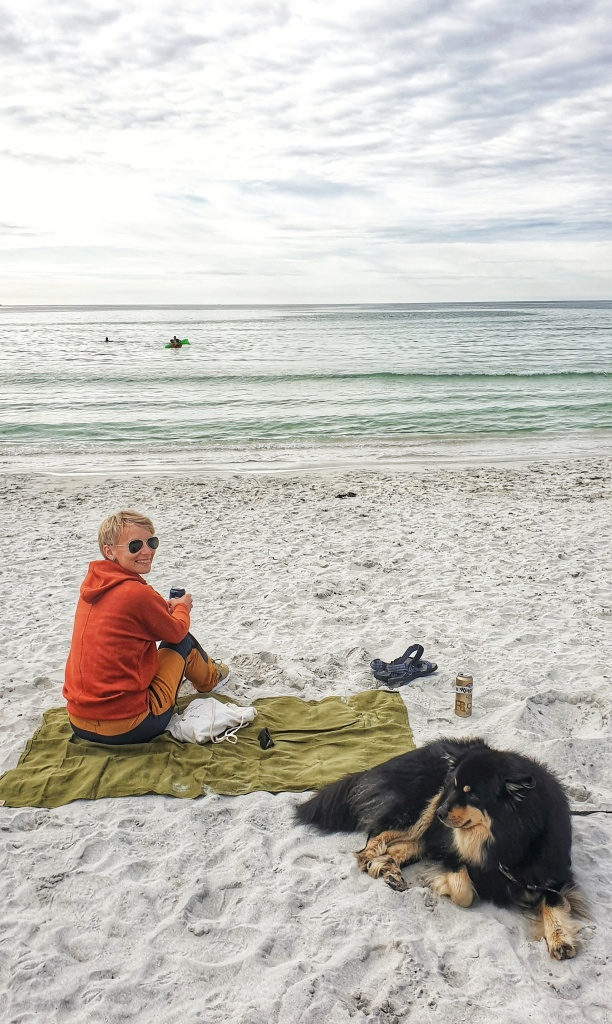A woman sitting on a blanket on Refviksanden beach with a dog next to her