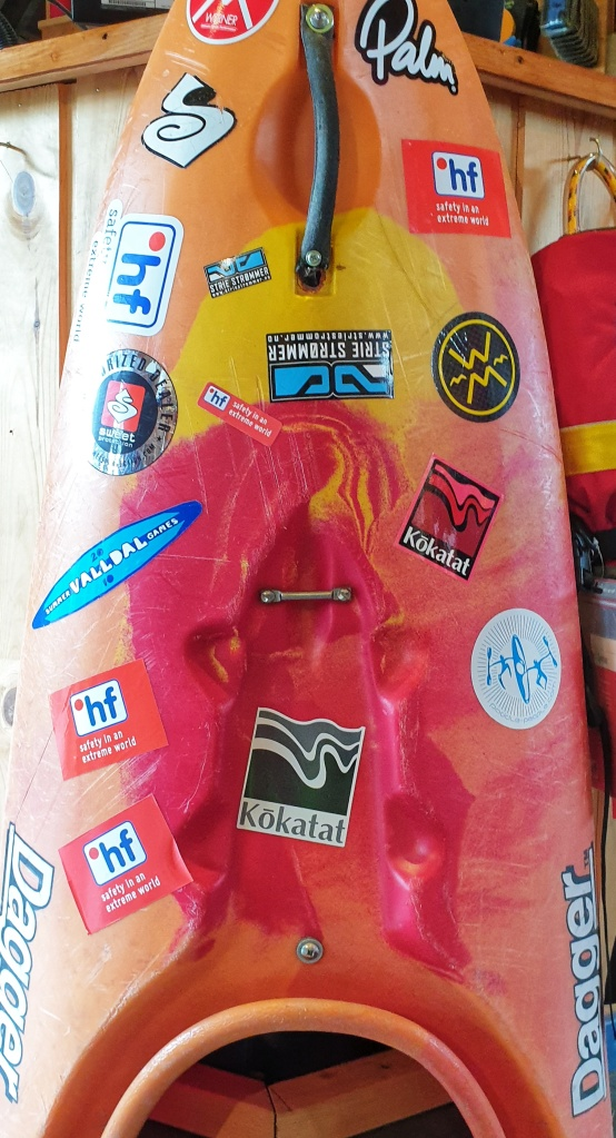 A red and orange white water kayak with stickers in Strie Strømmer in Heidal