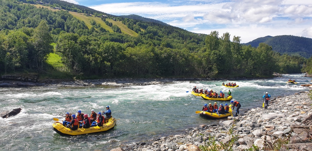 Six white water rafts coming down Sjoa river on a nice summer day