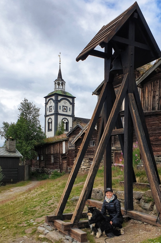 A woman in down jacket and hat sitting with a dog beneath a bell tower with Røros church behind.