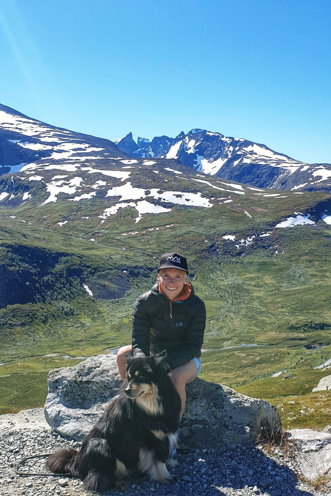 A woman in down jacket and jeans shorts with a dog in front of Skagastøltindan on Sognefjell