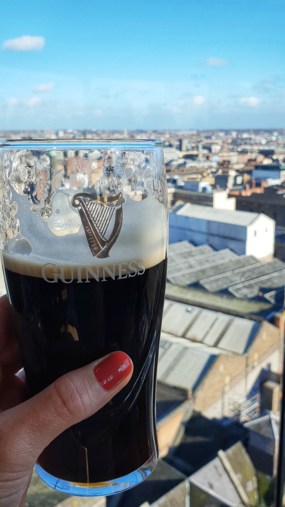 A hand with painted nails holding a pint of guiness in front of view of Dublin
