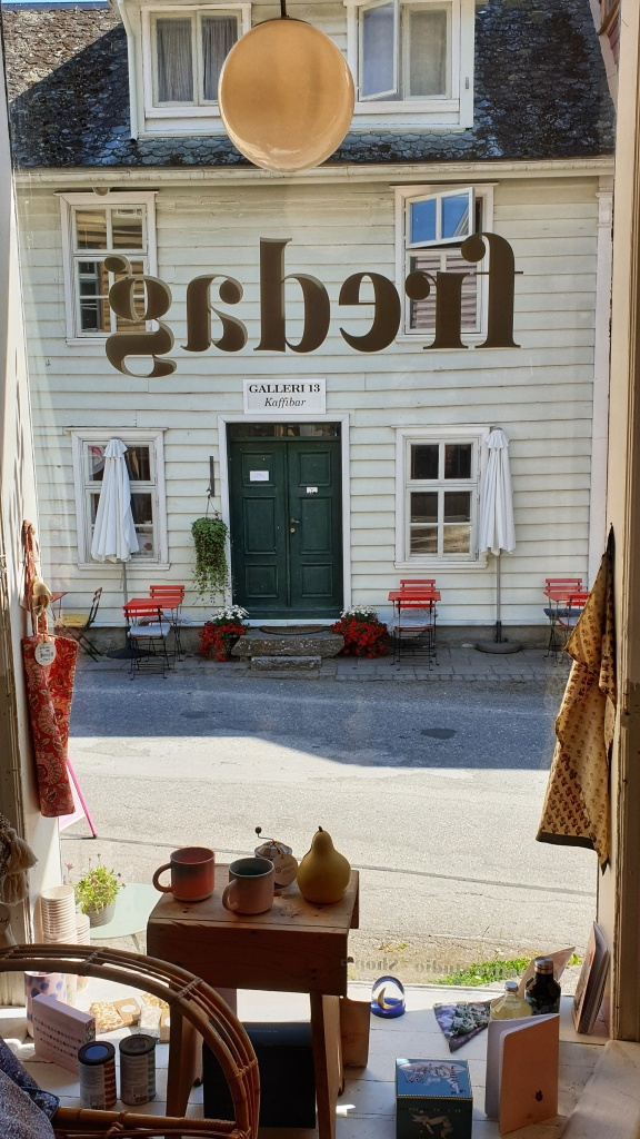 Street view from the window at Fredag in Lærdal, with items for sale in front