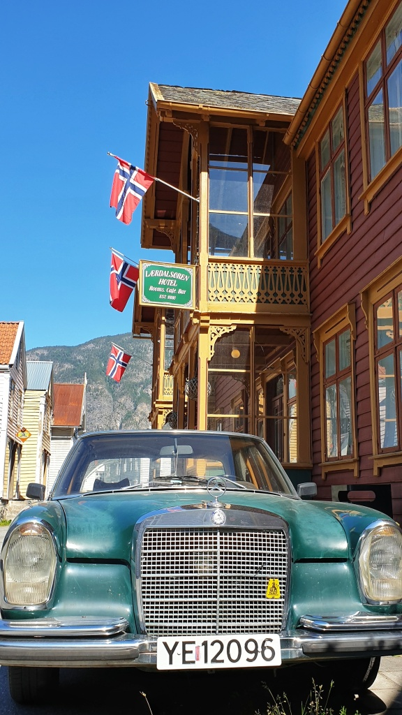 A  green veteran car outside a red swiss style hotel in old Lærdalsøyri