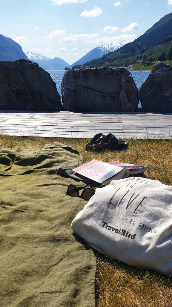 A cotton bag, a linen towel, book, sunglasses and sandals on a quay looking out on Jølstravatnet lake
