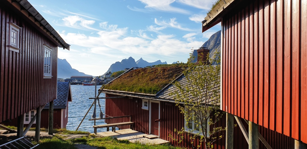 Red wooden huts with turf roof next to a bay. Houses, boats and mountains in the back.