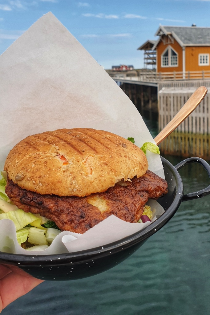 A bowl with a fish burger held over the sea. Quay and yellow boat house behind.