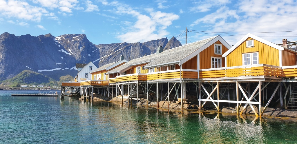 Yellow houses on stilts above clear sea, mountains behind.