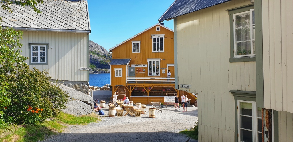 An outdoor café between old white and yellow houses in Nusfjord.