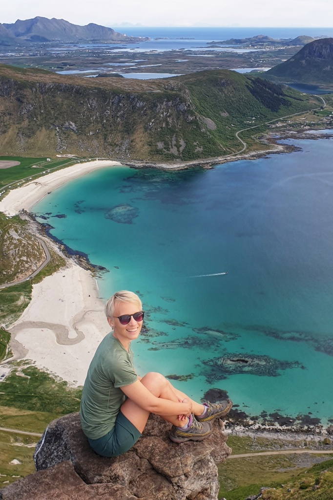 A woman dressed in green t-shirt and shorts sitting on a rock on Mt. Mannen over Hauklandstranda an Vik beaches.