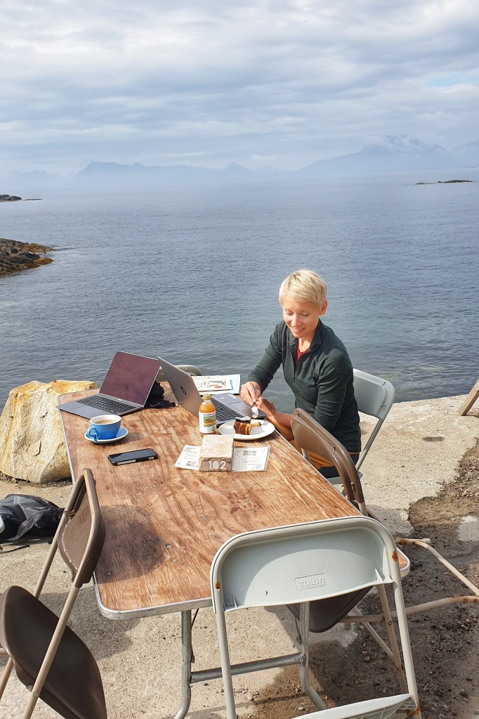 A woman eating cake with to laptops on a table by the sea at Trevarefabrikken.