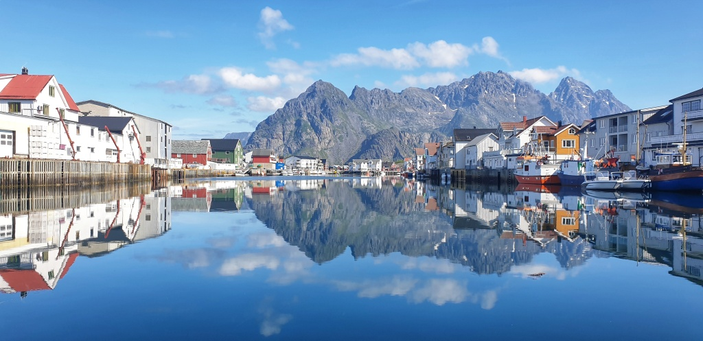 Henningsvær bay in sun. Boats and buildings lining the sides, mountains behind.
