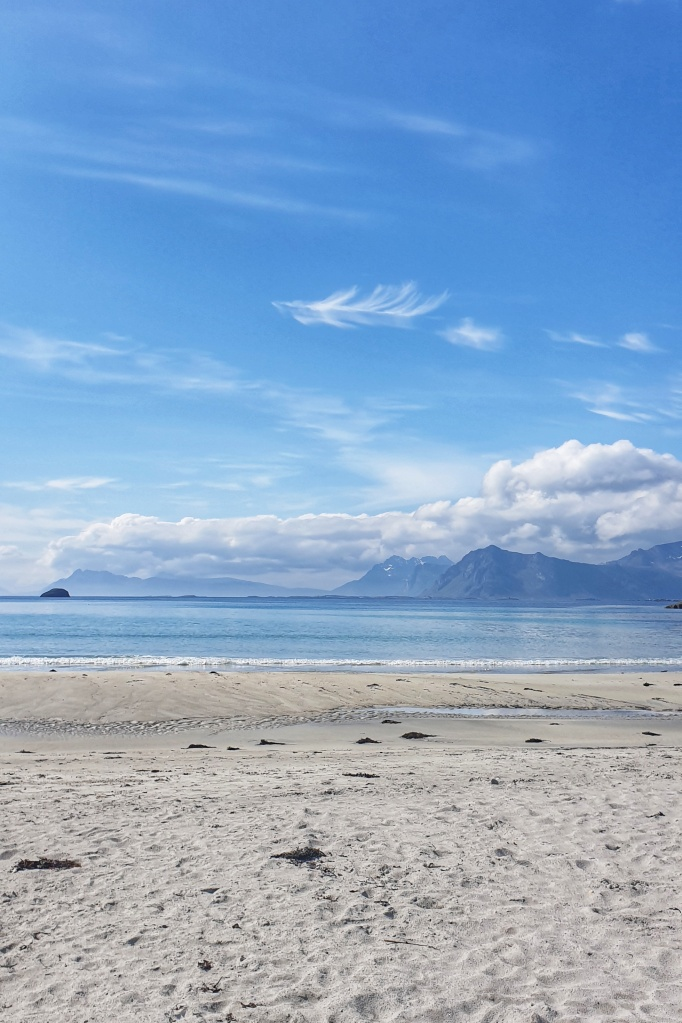 White beach, light blue sea, mountains and clouds in Lofoten.